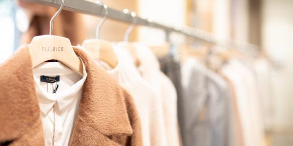 brown coat hanged on white plastic hanger